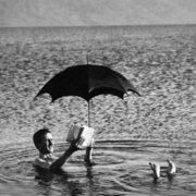 Man in sea with umbrella , Greeting Card