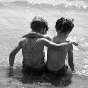Two children with arms around each other at beach, Greeting card